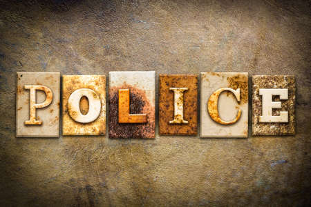 The word POLICE written in rusty metal letterpress type on an old aged leather background. Stock Photo