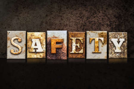 safeness: The word SAFETY written in rusty metal letterpress type on a dark textured grunge background.