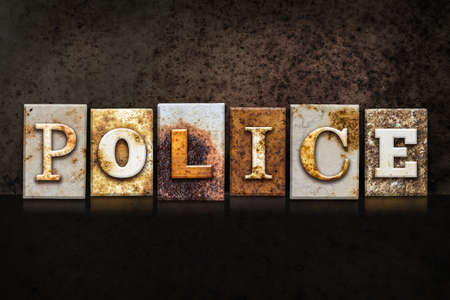 police unit: The word POLICE written in rusty metal letterpress type on a dark textured grunge background.