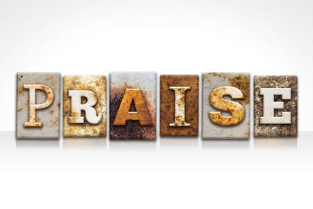 The word PRAISE written in rusty metal letterpress type isolated on a white background. Stock Photo