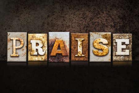 praised: The word PRAISE written in rusty metal letterpress type on a dark textured grunge background.