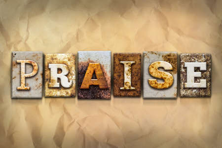 The word PRAISE written in rusty metal letterpress type on a crumbled aged paper background. Stock Photo