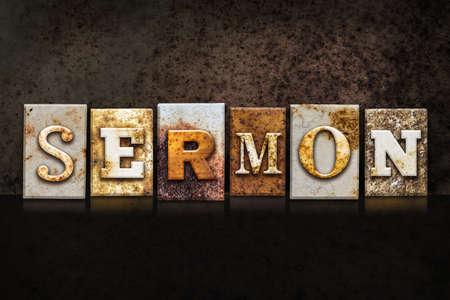 The word SERMON written in rusty metal letterpress type on a dark textured grunge background. Stock Photo