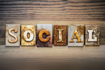 cordial: The word SOCIAL written in rusty metal letterpress type sitting on a wooden ledge background.