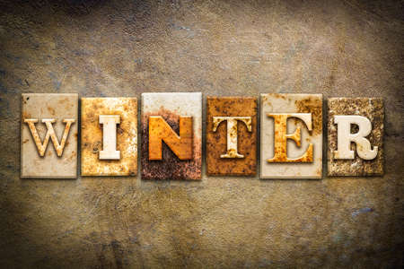 jack frost: The word WINTER written in rusty metal letterpress type on an old aged leather background.
