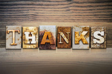 thankfulness: The word THANKS written in rusty metal letterpress type sitting on a wooden ledge background. Stock Photo