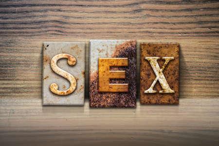 The word SEX written in rusty metal letterpress type sitting on a wooden ledge background.