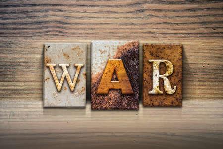 strife: The word WAR written in rusty metal letterpress type sitting on a wooden ledge background.