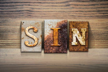 damnation: The word SIN written in rusty metal letterpress type sitting on a wooden ledge background.