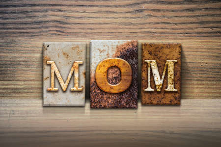 matron: The word MOM written in rusty metal letterpress type sitting on a wooden ledge background.