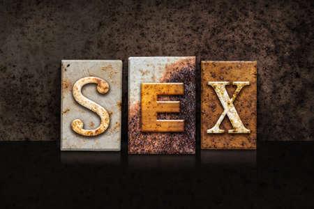 The word SEX written in rusty metal letterpress type on a dark textured grunge background.