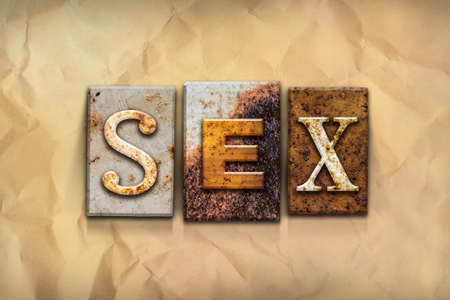 The word SEX written in rusty metal letterpress type on a crumbled aged paper background. Stock Photo