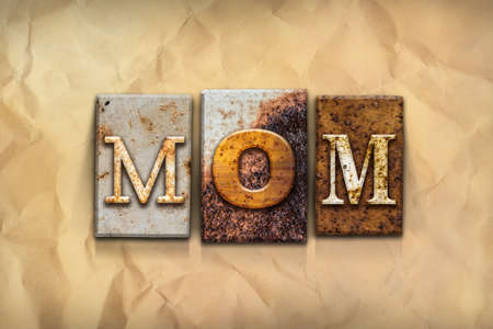 matron: The word MOM written in rusty metal letterpress type on a crumbled aged paper background.