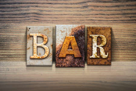 type bar: The word BAR written in rusty metal letterpress type sitting on a wooden ledge background.