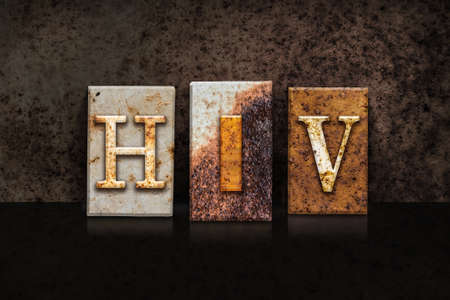 The word HIV  written in rusty metal letterpress type on a dark textured grunge background.