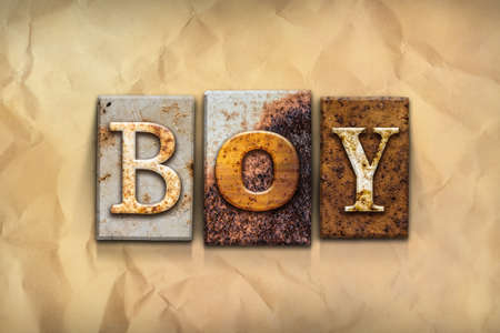 crumbled: The word BOY written in rusty metal letterpress type on a crumbled aged paper background. Stock Photo