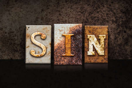 sinful: The word SIN written in rusty metal letterpress type on a dark textured grunge background.