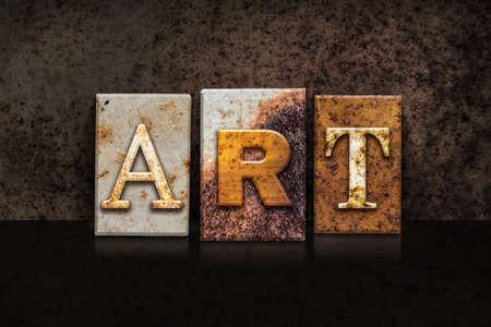 rust metal: The word ART written in rusty metal letterpress type on a dark textured grunge background. Stock Photo