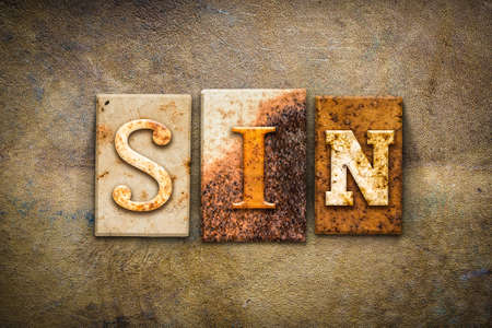damnation: The word SIN written in rusty metal letterpress type on an old aged leather background. Stock Photo