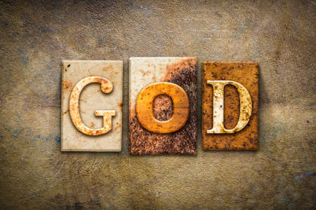 The word GOD written in rusty metal letterpress type on an old aged leather background.