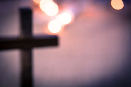 the religion: A background of bokeh lights with a soft, out of focus, wooden cross.