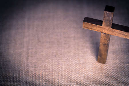 An aerial view of a holy wooden Christian cross on a burlap background.