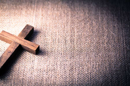holy cross: An aerial view of a holy wooden Christian cross on a burlap background.