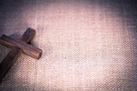 christian religion: An aerial view of a holy wooden Christian cross on a burlap background.