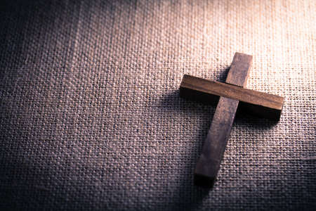 cruz religiosa: Una vista aérea de una cruz cristiana de madera santa sobre un fondo de arpillera.