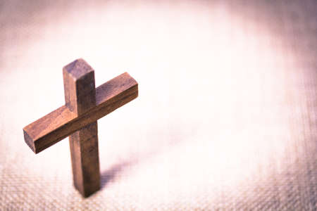 christian: An aerial view of a holy wooden Christian cross on a burlap background.