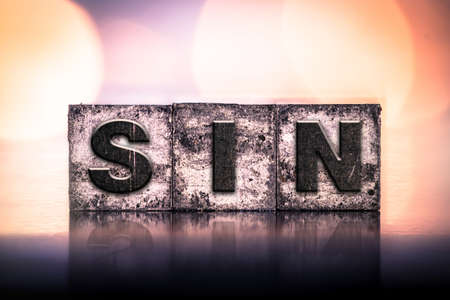 sin: The word SIN written in vintage ink stained letterpress type.