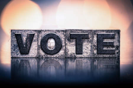 "The word ""VOTE"" written in vintage ink stained letterpress type."
