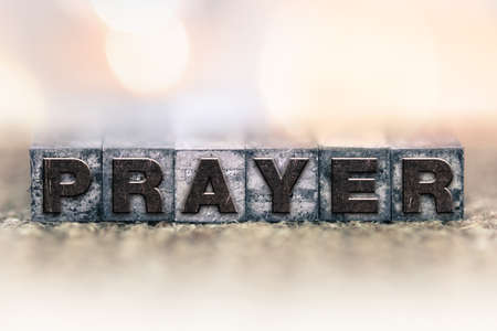 The word PRAYER written in vintage ink stained letterpress type. Stock Photo