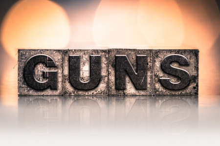 muzzleloader: The word GUNS written in vintage ink stained letterpress type.