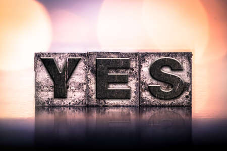 validation: The word YES written in vintage ink stained letterpress type. Stock Photo