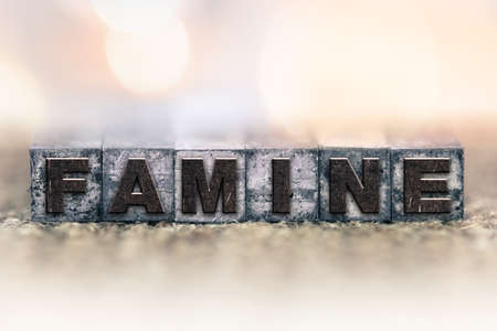 famine: The word FAMINE written in vintage ink stained letterpress type. Stock Photo
