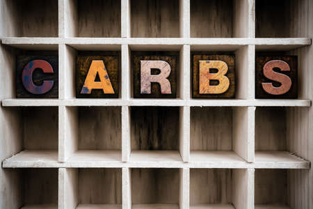 carbs: The word CARBS written in vintage ink stained wooden letterpress type in a partitioned printers drawer.