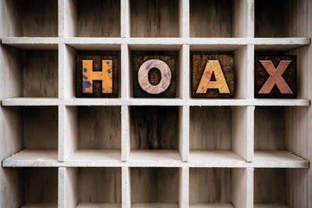 hoax: The word HOAX written in vintage ink stained wooden letterpress type in a partitioned printers drawer.