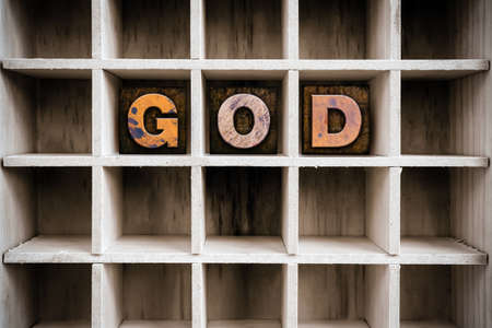 afterlife: The word GOD written in vintage ink stained wooden letterpress type in a partitioned printers drawer.
