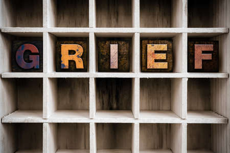 vigil: The word GRIEF written in vintage ink stained wooden letterpress type in a partitioned printers drawer. Stock Photo