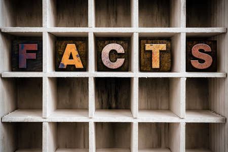 The word FACTS written in vintage ink stained wooden letterpress type in a partitioned printers drawer. Banco de Imagens