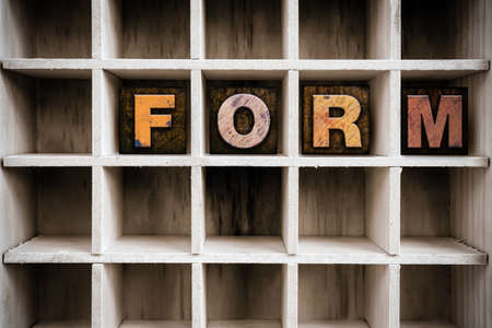 custom cabinet: The word FORM written in vintage ink stained wooden letterpress type in a partitioned printers drawer.