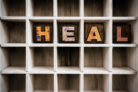 The word HEAL written in vintage ink stained wooden letterpress type in a partitioned printers drawer. Stock fotó