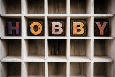 The word HOBBY written in vintage ink stained wooden letterpress type in a partitioned printers drawer. Imagens