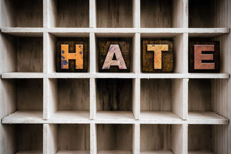 The word HATE written in vintage ink stained wooden letterpress type in a partitioned printers drawer.