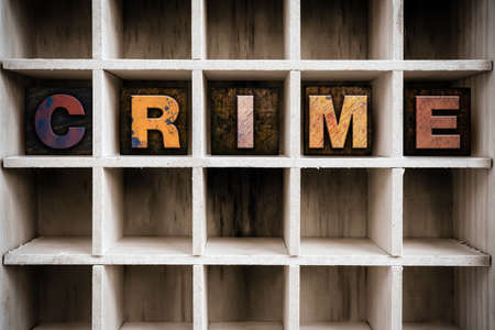 armed robbery: The word CRIME written in vintage ink stained wooden letterpress type in a partitioned printers drawer.