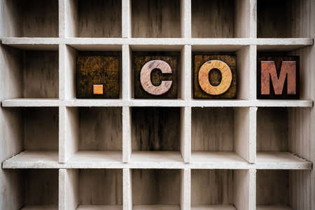 dot com: The word DOT COM written in vintage ink stained wooden letterpress type in a partitioned printers drawer. Stock Photo