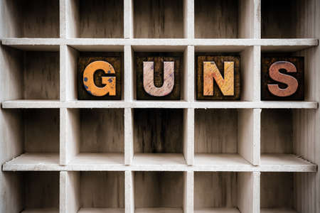 muzzleloader: The word GUNS written in vintage ink stained wooden letterpress type in a partitioned printers drawer.