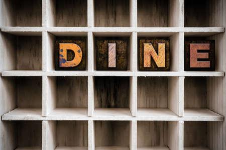 """Het woord """"DINE"""" geschreven in vintage inkt bevlekte houten letterzetseltype in lade een gepartitioneerd printer."""