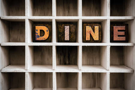 dine: The word DINE written in vintage ink stained wooden letterpress type in a partitioned printers drawer.